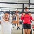 Постер, плакат: Athletes Doing Chin Ups At Gym