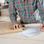 Carpenter Working On Blueprint While Measuring Wood — Stock Photo #56244285