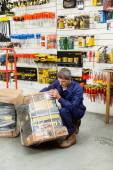Worker Lifting Tool Package In Hardware Shop — Stockfoto