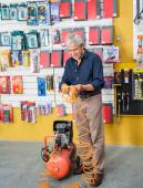 Senior Man Examining Air Compressor In Store — Stok fotoğraf