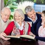 Happy Senior Couple Reading Book With Grandchildren In Nursing H — Stock Photo #56616671