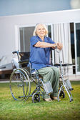 Senior Woman Sitting On Wheelchair At Nursing Home Lawn — Stock Photo