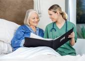 Caregiver Showing Medical Reports To Senior Woman — Stock Photo