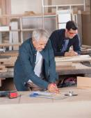 Male Carpenter Working On Blueprint At Workshop — Stock Photo
