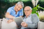Caretaker Assisting Senior Man In Using Digital Tablet — Stock Photo