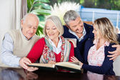 Happy Senior Couple Reading Book With Grandchildren In Nursing H — Stock Photo