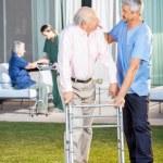 Caretaker Comforting Senior Man While Assisting Him At Lawn — Stock Photo #57259067
