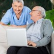 Caretaker With Senior Man Using Laptop On Couch — Stock Photo #57259125