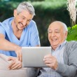Male Nurse And Senior Man Laughing While Using Digital Tablet — Stock Photo #57259707