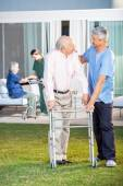 Caretaker Comforting Senior Man While Assisting Him At Lawn — Stockfoto