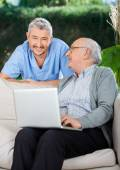 Caretaker With Senior Man Using Laptop On Couch — Stock Photo