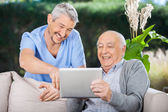Male Nurse And Senior Man Laughing While Using Digital Tablet — Stock Photo