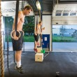 Athletes Exercising On Gymnastic Rings At Healthclub — Stock Photo #57261065