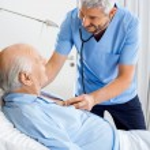 Smiling Caretaker Checking Senior Mans Chest — Stock Photo #57261761