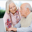 Senior Couple Looking At Each Other While Using Laptop — Foto Stock #57263943