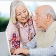 Senior Couple Looking At Each Other While Using Laptop — Stockfoto #57263943