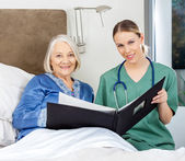 Nurse And Senior Woman With Medical Reports In Bedroom — Stock Photo