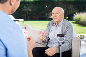 Male Caretaker And Senior Man Playing Cards — Stock Photo