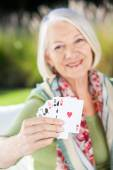 Happy Senior Woman Showing Playing Cards — Stock Photo