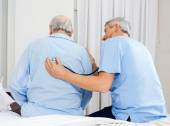 Caretaker Examining Senior Mans Back — Stock Photo