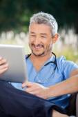 Male Nurse Smiling While Looking At Tablet Computer — Stock Photo