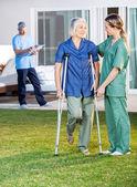 Female Nurse Helping Senior Woman To Use Crutches — Stockfoto
