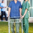 Nurse Assisting Senior Woman To Walk With Zimmer Frame — Stock Photo #57276835