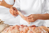 Butcher Holding Raw Chicken Piece In Butchery — Stock Photo