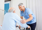 Caretaker Helping Senior Man To Use Walking Frame — Stock Photo