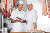 Happy Butchers With Digital Tablet At Counter — Stock Photo