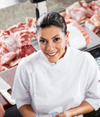 Confident Female Butcher Standing At Display Cabinet — Stockfoto