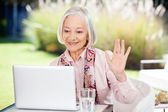 Senior Woman Waving While Video Chatting On Laptop — Stock Photo