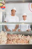 Confident Butchers Smiling At Display Cabinet — Stockfoto