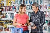 Couple Paying Pliers Through Smartphone In Hardware Store — Stock Photo