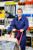 Worker Pushing Trolley In Hardware Shop — Stock Photo