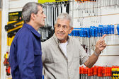Customer Pointing While Looking At Hardware Shop Vendor — Stock Photo