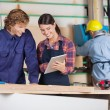 Carpenters Using Digital Tablet In Workshop — Stock Photo #57458561