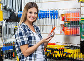 Customer Holding Cellphone And Screwdriver In Store — Stockfoto
