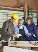 Dijital Tablet meslektaşı ile tartışırken tutan bir marangoz — Stok fotoğraf