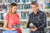 Couple Paying For Flashlight Through Smartphone In Store — Stock Photo