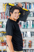 Smiling Man Carrying Toolbox On Shoulder In Store — Stockfoto