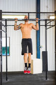 Male Athlete Doing Chin-Ups At Healthclub — Stock Photo