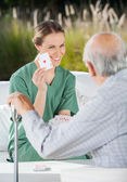 Smiling Female Caretaker Showing Ace Card To Senior Man — Stock Photo