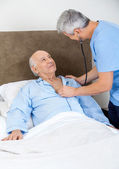Caretaker Checking Senior Man With Stethoscope — Stock Photo
