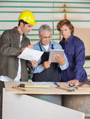 Carpenters Discussing Over Digital Tablet And Paper — Foto de Stock