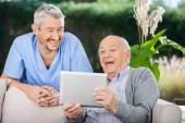 Male Caretaker And Senior Man Using Tablet PC — Stock Photo