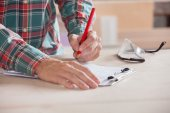 Carpenter Writing Notes On Clipboard At Table — Stock Photo