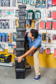 Man Carrying Stacked Heavy Toolboxes In Shop — Stock Photo