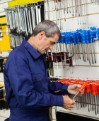 Vendor Examining Screwdriver In Shop — Stock Photo