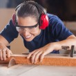 Female Carpenter Cutting Wood With Tablesaw — Stock Photo #58507559